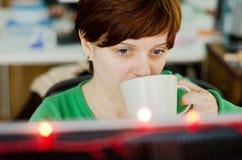 Kvinna som dricker kaffe på arbete arkivfoto