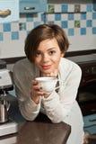 Kvinna som dricker kaffe på kök. Arkivbild