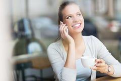 Kvinna som dricker kaffe på kafét Arkivfoton