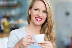 Kvinna som dricker kaffe på kafét Arkivfoto