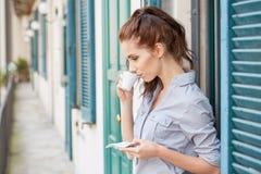 Kvinna som dricker kaffe på terrassen på en morgon Arkivbild