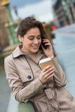 Kvinna som dricker kaffe som talar på mobiltelefonen, London, England Arkivfoton