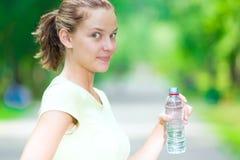Kvinna som dricker kall mineralvatten från en flaska efter konditionföre detta Arkivfoto