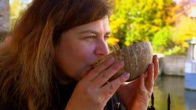 Kvinna som dricker kokosnötöl från bunken i Belgien gatakafé stock video