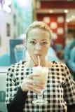 Kvinna som dricker milkshaken i matställe Royaltyfria Bilder