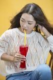 Kvinna som dricker ny fruktsaft vid sugrör Royaltyfria Bilder