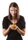 Kvinna som dricker orange fruktsaft Arkivbild