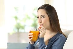 Kvinna som dricker orange fruktsaft med ett sugrör Royaltyfri Fotografi