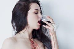 Kvinna som dricker rött vin, som kör ner henne armar och bröstkorgen Royaltyfri Fotografi