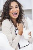 Kvinna som dricker te eller kaffe genom att använda minnestavladatoren Royaltyfri Fotografi