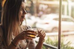 Kvinna som dricker te på kafét med soluppgång som in strömmar till och med fönster och skapar signalljuset in i linsen arkivbild