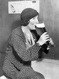Kvinna som dricker ut ur ett stort ölexponeringsglas (alla visade personer inte är längre uppehälle, och inget gods finns Leveran Arkivbild