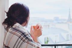 Kvinna som dricker varmt te och hemma ser fönstret, hemtrevlig vinter royaltyfria foton
