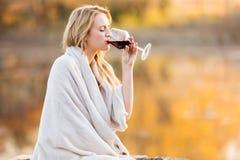 Kvinna som dricker vinsolnedgång Arkivbild