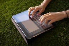 Kvinna som Emailing och smsar med minnestavladatoren på gräs Fotografering för Bildbyråer