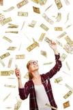 Kvinna som fångar regna dollarpengar Arkivbild