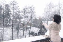 Kvinna som fångar snöflingor med båda händer arkivfoto
