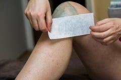 Kvinna som får ben vaxade för hårborttagning i hem fotografering för bildbyråer
