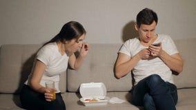 Kvinna som får borrad medan man som tar lek på mobiltelefonen på hemmet lager videofilmer