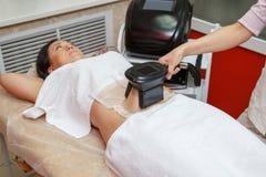 Kvinna som får cryolipolysis fet behandling i yrkesmässigt kosmetiskt kabinett arkivfoto