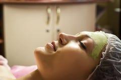 Kvinna som får den ansikts- omsorgskalningsmaskeringen av kosmetologen på brunnsortsaloen Arkivfoton