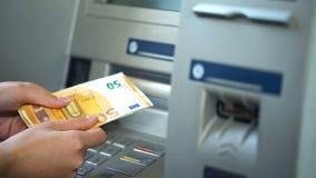 Kvinna som får euro från maskinen för automatisk kassör, kassa som återtar och att packa ihop royaltyfri bild