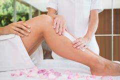 Kvinna som får henne ben vaxade av skönhetterapeuten royaltyfri foto