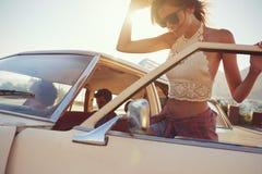Kvinna som får in i bilen för vägtur med vänner royaltyfria bilder