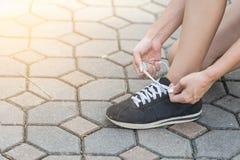 Kvinna som får klar att köra och binder rinnande skor royaltyfri foto