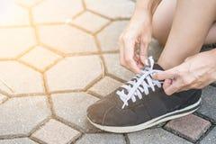 Kvinna som får klar att köra och binder rinnande skor arkivbild
