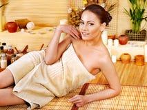 Kvinna som får massage i bambubrunnsort. Arkivfoto