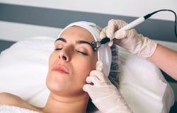 Kvinna som får rf som omkring lyfter av ögon i klinik arkivfoto