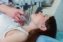 Kvinna som får ultraljudet av en sköldkörtel från doktor arkivfoton