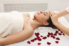 Kvinna som får yrkesmässig ansikts- massage på brunnsortsalongen arkivfoto