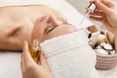 Kvinna som får yrkesmässig ansikts- massage på brunnsortsalongen royaltyfria bilder