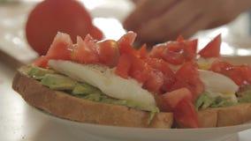 Kvinna som förbereder den sunda frukosten med avokadot på den grillade bröd, ägg och tomaten lager videofilmer