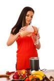 Kvinna som förbereder den sunda smoothien för ny frukt Fotografering för Bildbyråer