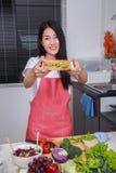 Kvinna som förbereder en smörgås i kökrum royaltyfria bilder