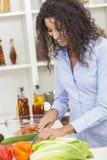 Kvinna som förbereder grönsaksalladmat i kök Fotografering för Bildbyråer
