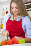 Kvinna som förbereder grönsaksalladmat i kök Royaltyfri Bild