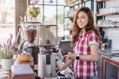 Kvinna som förbereder kaffe med maskinen i kafé arkivfoton
