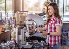 Kvinna som förbereder kaffe med maskinen i kafé royaltyfri bild