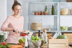 Kvinna som förbereder vegetariskt mål royaltyfri fotografi
