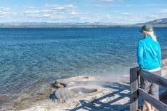 Kvinna som förbiser geyseren på kusten av Yellowstone sjön Arkivbilder