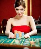 Kvinna som förlägger en vad på kasinot royaltyfri foto