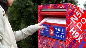Kvinna som förlägger post i en kanadensisk brevlåda stock video
