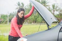 Kvinna som försöker att fixa hennes brutna bil royaltyfri bild