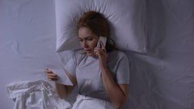 Kvinna som försöker att kalla till hennes man som ligger i säng och ser fotoet, svek stock video