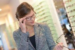 Kvinna som försöker olika parexponeringsglas, innan att göra val Arkivfoto