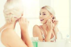 Kvinna som försöker på örhänget som ser badrumspegeln arkivfoto
